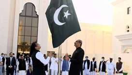 Pakistan ambassador Syed Ahsan Raza, right, hosting the national flag to mark the Independence Day o