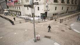 A pedestrian wearing a protective mask walks along Wall Street in front of the New York Stock Exchan