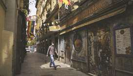 A pedestrian walks along a side street lined with shuttered restaurants in Madrid. CEOE, Spain's mai