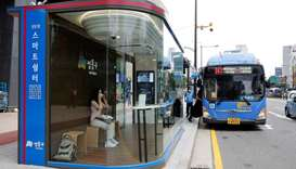 A woman wears a mask inside a glass-covered bus stop in which a thermal imaging camera, UV sterilize