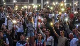 Belarus opposition supporters raise their mobile phones with flashlights during a symbolic minute of