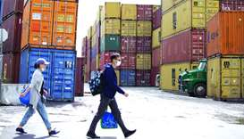 Pedestrians walk past shipping containers at Ray-mont Logistiques in Montreal. Export and import vol