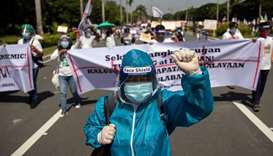 A healthworker in hazmat suit joins the protest ahead of Philippine President Rodrigo Duterte's fift