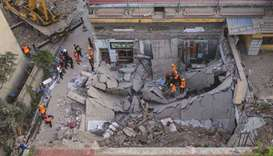 This aerial view taken yesterday shows rescuers searching through the rubble of a collapsed restaura