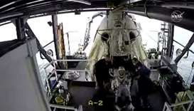 An opened hatch of the capsule carrying NASA astronauts is seen as one of the astronauts exits it in