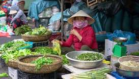 A woman wearing a protective mask sells vegetables during the coronavirus disease outbreak in Hoi An