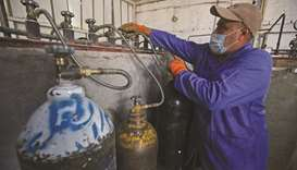File photo shows a mask-clad worker refilling oxygen cylinders at a factory in Taji district, north