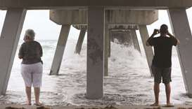 Residents watch the waves kicked up by Tropical Storm Isaias along the Deerfield Beach International