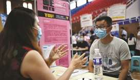 A job seeker (right) speaking with a recruiter of a company during a career fair in Zhengzhou, China