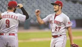 Trevor Bauer (right) of the Cincinnati Reds smiles as he is greeted by Mike Moustakas after their wi