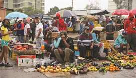 Sellers wait for customers under the rain at the Coche wholesale market amid coronavirus (Covid-19)