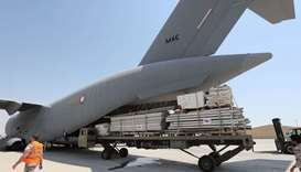 Workers load a plane as Qatar begins sending field hospitals and medical aid to Lebanon from the al-
