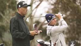 "Justin Thomas of the United States hits a tee shot as his caddie, Jim ""Bones"" Mackay looks on during"