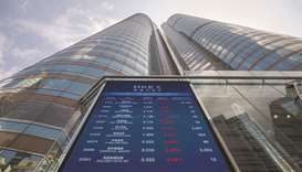 A screen displays stock figures outside the Hong Kong Stock Exchange. The Hang Seng closed down 1.6%