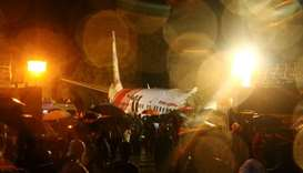 Rescue workers look for survivors after a passenger plane crashed when it overshot the runway at the