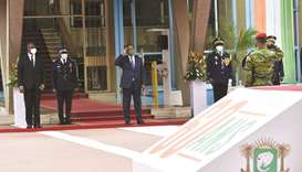 Ivory Coast President Alassane Ouattara, flanked by Ivorian Prime Minister Hamed Bakayoko, salutes d