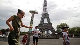 People cool off under a water spray as a heatwave rolls over Paris, France