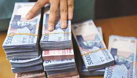 Bundles of Indonesian rupiah banknotes seen on a desk at a currency exchange office in Jakarta. Rupi