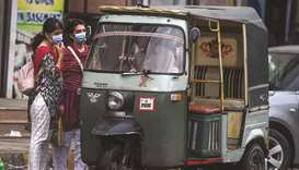 Women wearing face masks are seen speaking with an auto-rickshaw driver in Karachi. Data has reveale