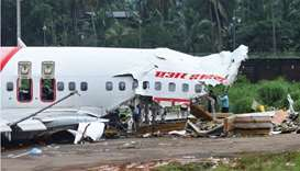 Officials inspect the site where a passenger plane crashed when it overshot the runway at the Calicu