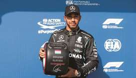 Mercedes' British driver Lewis Hamilton poses with the pole position award after winning the the qua