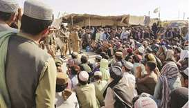 Pakistan Army soldiers address people gathered at the Friendship Gate crossing point in the Pakistan
