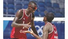 Cherif Younousse (left) and Ahmed Tijan of Qatar celebrate a point during the beach volleyball Round