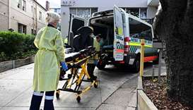 Health workers take out stretchers from an ambulance at the Hardi Aged Care Nursing Home Facility in