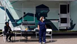 Nurses wait for people to come by to receive their coronavirus disease vaccine at a mobile pop-up va