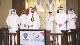 Sheikh Mohamed rings in bell to mark Mekdam's foray into the Qatar Stock Exchange as others look on.