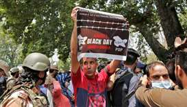 A supporter of the Peoples Democratic Party (PDP), a pro-India political party, holds up a poster du