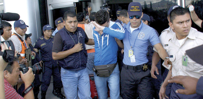 Policemen escort one of five Syrian men detained at Toncontin international airport in Tegucigalpa,