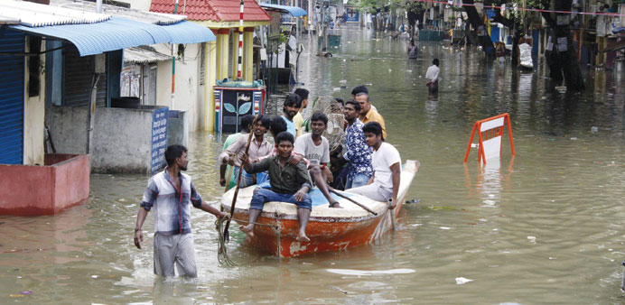 Volunteers with a boat move people to safety on a flooded street of Chennai yesterday.