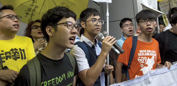 Students leaders Nathan Law (left), Alex Chow and Joshua Wong (right) chant slogans as they arrive a
