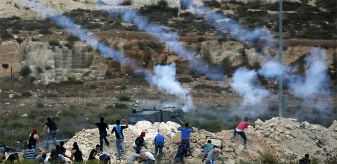 Israeli security forces fire tear gas towards Palestinian students throwing stones during clashes