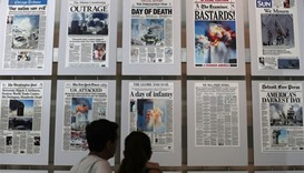 Visitors browse newspaper front pages with the story of the 9/11 terror attacks at the 9/11 Gallery