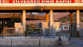A man sits in front of the Turkish Cilvegozu border gate