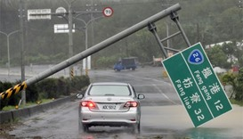 A car drives pass a collapsed traffic sign, toppled by strong winds of typhoon Meranti