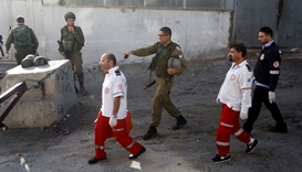 Israeli forces and Palestinian medics walk near the scene of what the Israeli military said was a st
