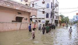 Residents make their way through floodwaters following heavy rain in Nizampet, a low lying area on t