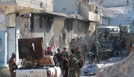 Syrian government forces gather amidst destruction in the deserted Palestinian refugee camp of Handa