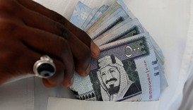 A Saudi man shows Saudi riyal banknotes at a money exchange shop, in Riyadh, Saudi Arabia, January 2