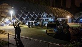 Policemen stand in front of an airdome housing a refugee shelter