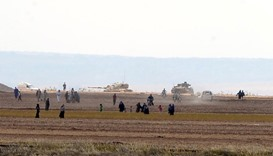 Syrian civilians, with Turkish Army tanks in the background, walk through the Turkish border