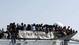Migrants wait to disembark from the Italian Navy vessel Sfinge in the Sicilian harbour of Pozzallo