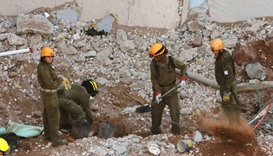 Israeli rescue workers sift through the rubble at the site where a building collapsed in Ramat Hahay