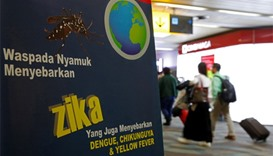 passengers walk past a banner about the Zika virus