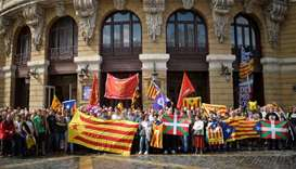 Protesters carry Esteladas, Catalan separatist flags and Basque flags, during a rally