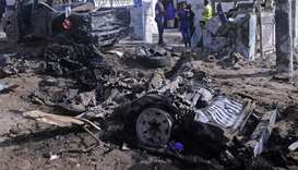 Somali soldiers stand on the scene of a suicide car bomb attack