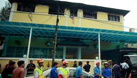 Malaysian Fire and Rescue personnel stand outside the Darul Quran Ittifaqiyah religious school in Ku